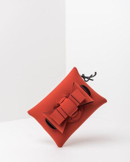 La foto ritrae una borsa modello pochette della linea Chérie di APbag. Si tratta di una borsa lavabile effetto neoprene, disegnata da Stefano Galandrini, prodotta e distribuita da Artpelle.it La borsa è di colore cotto.