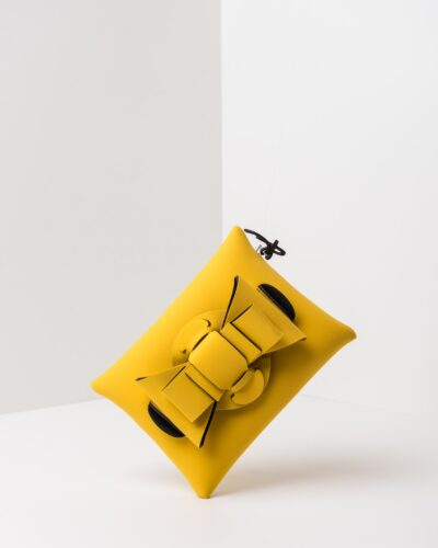 La foto ritrae una borsa modello pochette della linea Chérie di APbag. Si tratta di una borsa lavabile effetto neoprene, disegnata da Stefano Galandrini, prodotta e distribuita da Artpelle.it La borsa è di colore giallo.